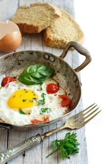 Gebakken ei met tomaten, zelfgebakken brood en kruiden op een oude koekenpan op hout