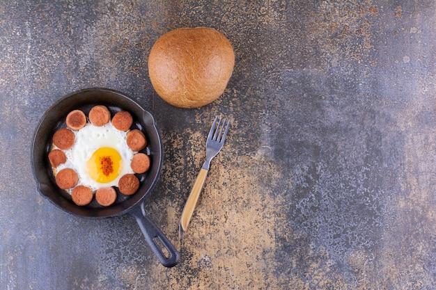 Gebakken ei met worstjes in een pan en een broodje erbij