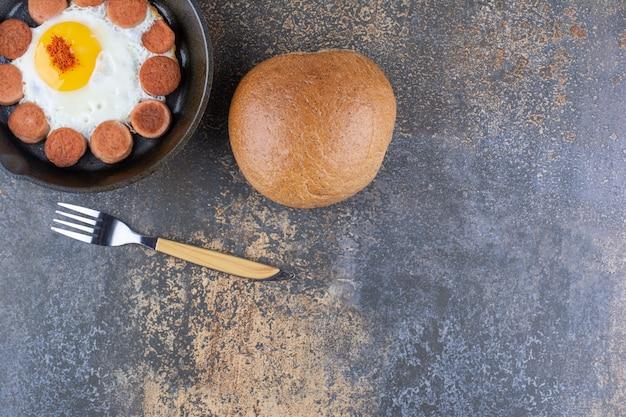 Gebakken ei met worstjes in een pan geserveerd met een broodje