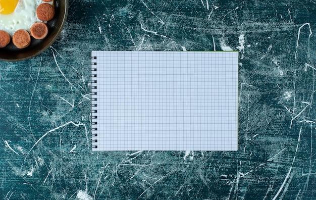 Gebakken ei met worstjes in een pan met een blanco notitieboekje opzij.