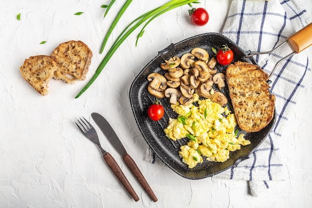 Gebakken ei op een koekenpan. gezouten en gekruid gebakken ei met champignonpaddestoelen op gietijzeren pan en lichte tafel. plaats voor tekst, bovenaanzicht.