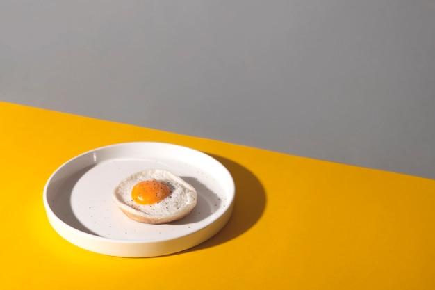 Gebakken ei op een witte plaat op een gele achtergrond met schaduwen