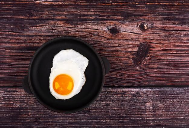 Gebakken ei op koekenpan, op houten achtergrond. bovenaanzicht.