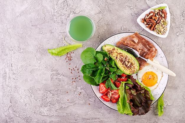 Gebakken ei, spek, avocado, rucola en aardbeien