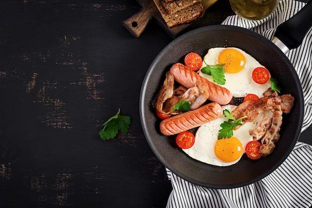 Gebakken ei, tomaten, worst en spek