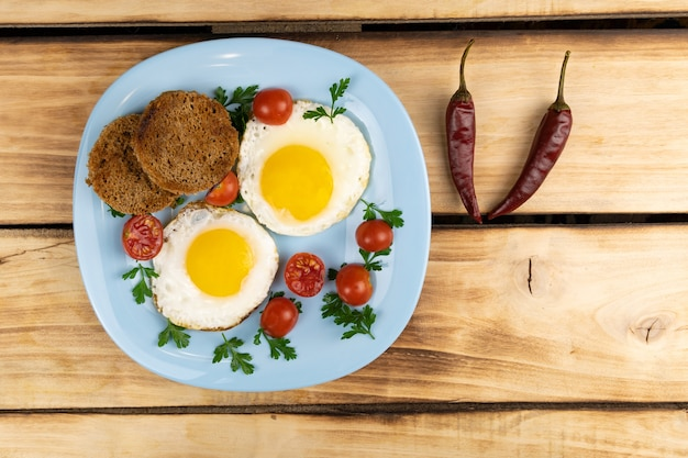 Gebakken eieren, broodcroutons, kerstomaatjes, peterselie op een blauw bord.