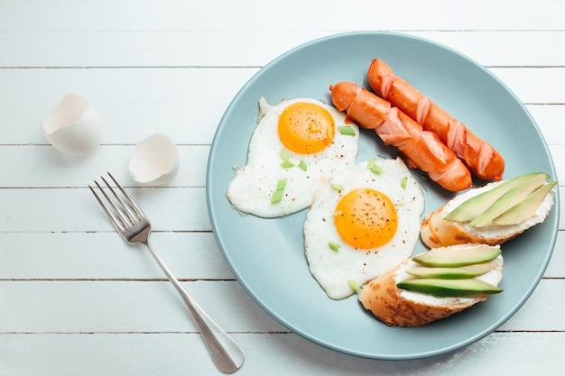 Gebakken eieren en avocado sandwich op een blauw bord