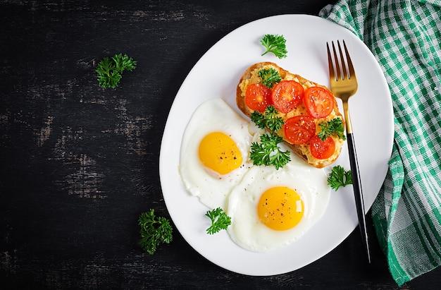 Gebakken eieren en een broodje gegrilde kip pate op een donkere achtergrond. bovenaanzicht, overhead