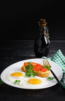 Gebakken eieren en een broodje gegrilde kip pate op een donkere achtergrond.