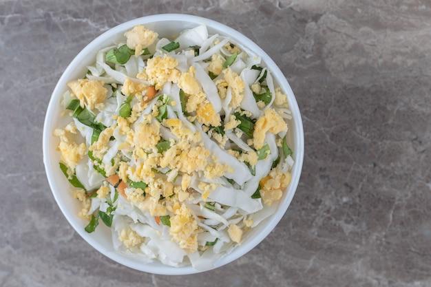 Gebakken eieren en verse salade in witte kom.