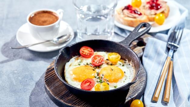 Gebakken eieren. gebakken eieren van twee eieren in gietijzeren pan met kerstomaatjes en microgreens, toast en kopje koffie. zonnig ochtendontbijtconcept
