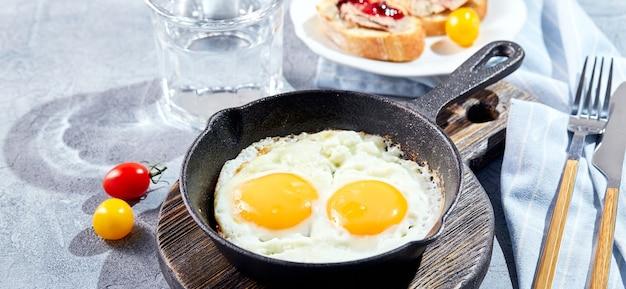 Gebakken eieren. gebakken eieren van twee eieren in gietijzeren pan met kerstomaatjes, toast. zonnige ochtend ontbijt concept banner