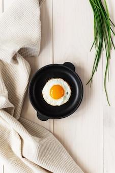Gebakken eieren in een gietijzeren koekenpan met groene uien en een linnen handdoek