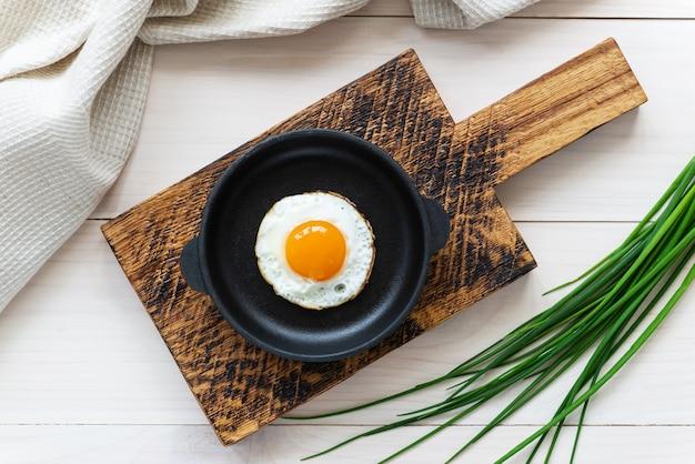 Gebakken eieren in een gietijzeren koekenpan op een houten bord met groene uien en een linnen handdoek