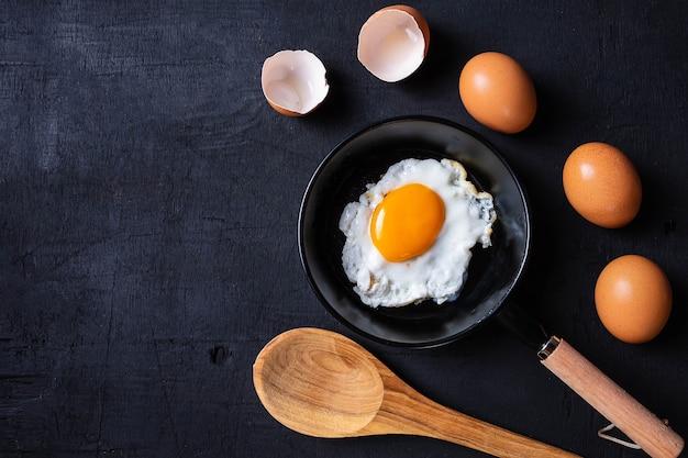 Gebakken eieren in een koekenpan en eierschaal voor het ontbijt op een zwarte achtergrond.