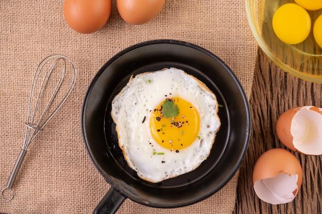 Gebakken eieren in een koekenpan en rauwe eieren, biologisch voedsel voor een goede gezondheid, rijk aan eiwitten