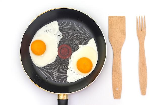 Gebakken eieren in een koekenpan met een houten vork en spatel op wit wordt geïsoleerd. bovenaanzicht
