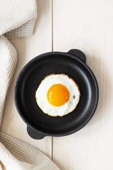 Gebakken eieren in een koekenpan op een houten tafel