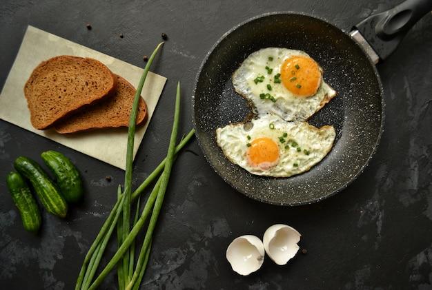 Gebakken eieren in een pan. eieren, groene uien, bruin brood, komkommers.