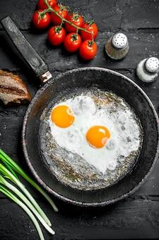 Gebakken eieren in een pan met brood en tomaten. op zwarte rustieke achtergrond.