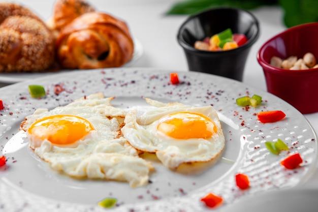 Gebakken eieren in een plaat met een gebakje op achtergrond. bovenaanzicht.