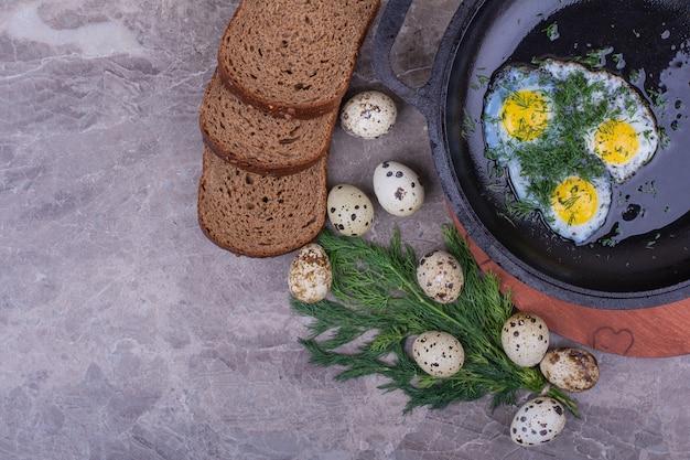 Gebakken eieren in een zwarte pan met kruiden en brood