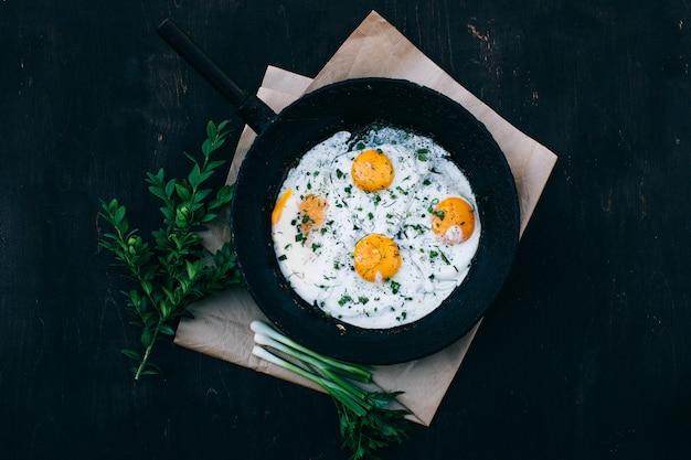 Gebakken eieren in gietijzeren koekenpan op donker hout