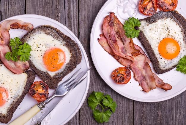 Gebakken eieren in roggebrood met spek, tomaten en peterselie in rustieke stijl.