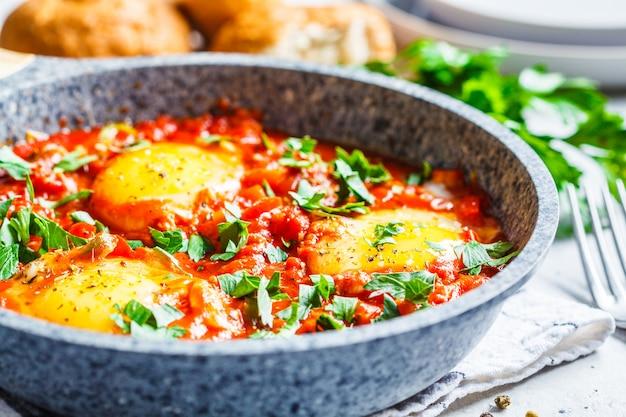 Gebakken eieren in tomatensaus met kruiden