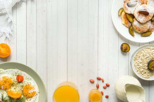 Gebakken eieren, kwark pannenkoeken, pruimen en havermout met melk, sinaasappelsap op tafel