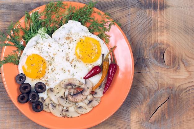 Gebakken eieren met champignons, olijven, dille en rode chili peper