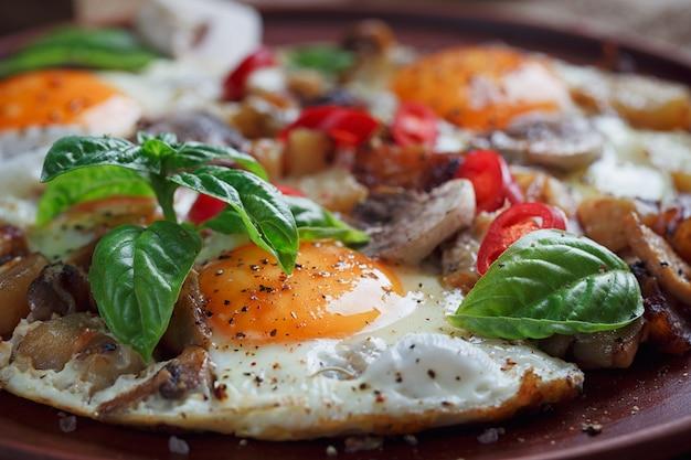 Gebakken eieren met champignons, tomaten en basilicum op rustieke houten tafel.
