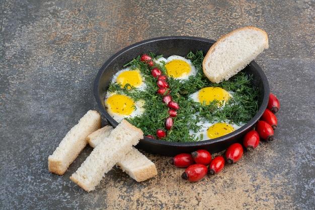 Gebakken eieren met dille, granaatappelpitjes en sneetjes brood.