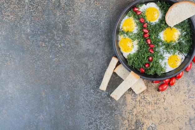 Gebakken eieren met dille, granaatappelpitjes en sneetjes brood