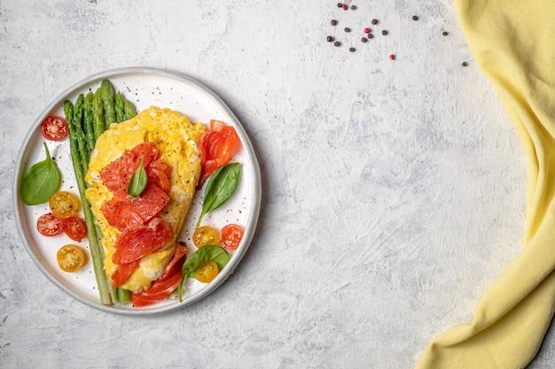 Gebakken eieren met groene asperges en zalm, cherrytomaatjes en verse spinazie.