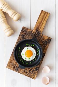 Gebakken eieren met groene uien en kruiden in een gietijzeren koekenpan
