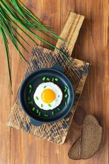 Gebakken eieren met groene uien in een gietijzeren koekenpan op een houten plank a