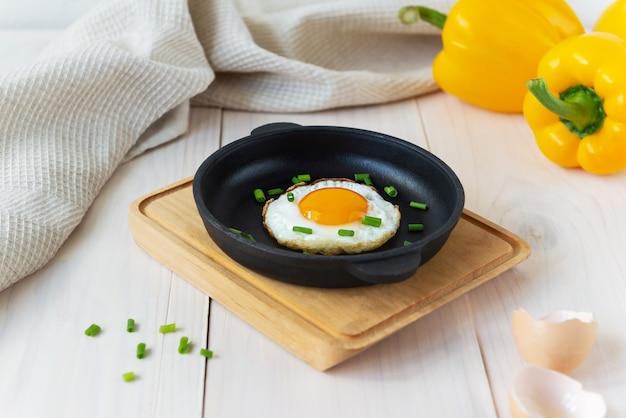 Gebakken eieren met groene uien in een gietijzeren koekenpan