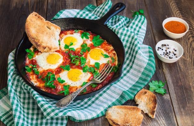 Gebakken eieren met groenten en tomatensaus in ijzeren koekenpan op rustieke houten achtergrond