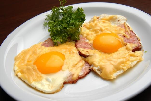 Gebakken eieren met ham en kaas op een plaat