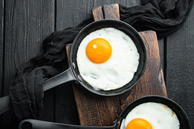 Gebakken eieren met kerstomaatjes en brood voor het ontbijt in gietijzeren koekenpan, op zwarte houten tafel, bovenaanzicht plat lag