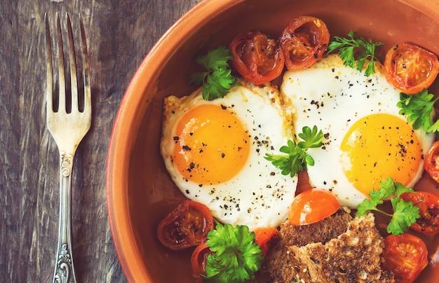Gebakken eieren met kerstomaatjes en peterselie in kleischotel op rustieke houten achtergrond