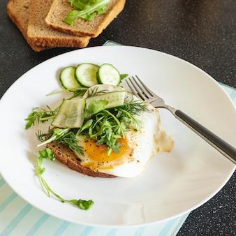 Gebakken eieren met komkommer en brood op een zwarte tafel