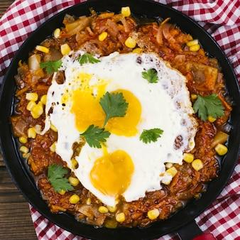 Gebakken eieren met mexicaans eten in een pan