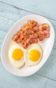Gebakken eieren met reepjes spek op de witte plaat