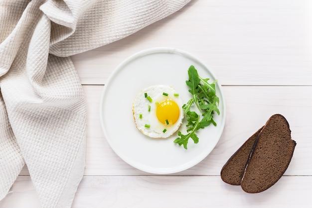 Gebakken eieren met rucola in een bord brood en linnen handdoek op een houten tafel