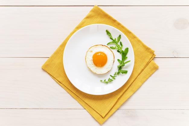 Gebakken eieren met rucola in een bord op een geel linnen servet
