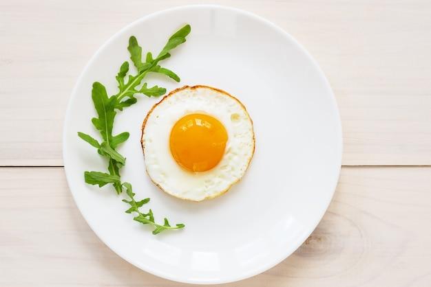 Gebakken eieren met rucola in een bord