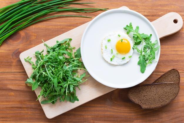 Gebakken eieren met rucola op een bord op een bruin houten tafel