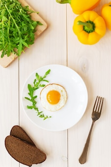 Gebakken eieren met rucola paprika en brood op een houten tafel